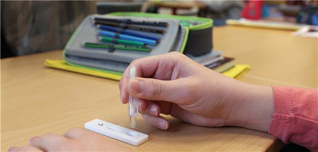 Eine Schülerin träufelt in einem Klassenraum eine Lösung nach einem selbst durchgeführten Corona-Test auf einen SARS-CoV-2-Antigentest. Pädiater lehnen regelmäßige Schnelltests allerdings ab.